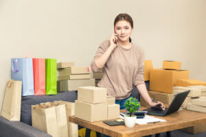 woman packing boxes using ecommerce shipping strategy