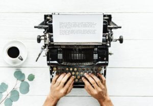 hands typing on manual typewriter in ecommerce blogging