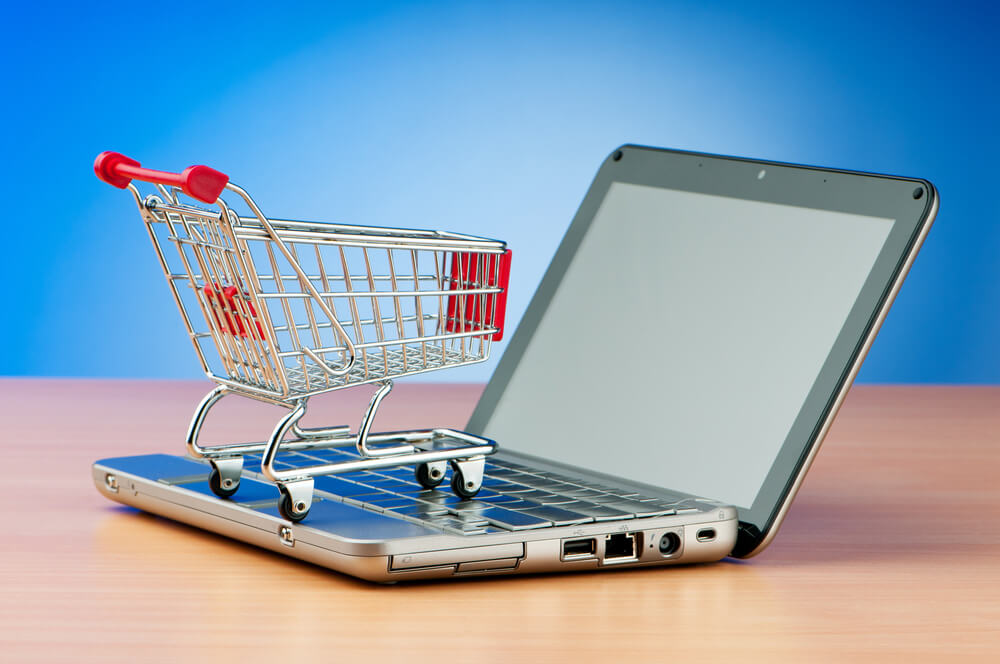 shopping cart on laptop helps to organize an ecommerce site
